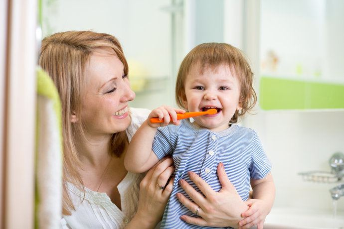 Baby with orange toothbrush and mother watching.