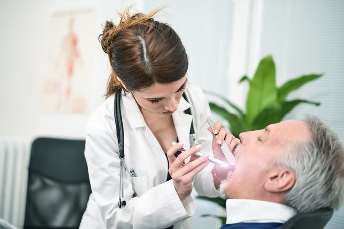Dr. Looking the mouth of a patient with torch.