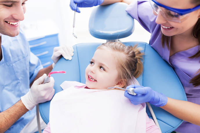 Young girl in a dentist's chair smiling showing teeth.